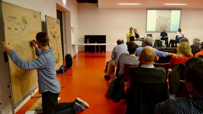 Graphic Recording des Eröffnungsvortrags und -Panels: Jakob Kohlbrenner (Grafiker); auf dem Podium: Astrid Ley, Roderick Lawrence und Steve Ouma Akoth (von links)